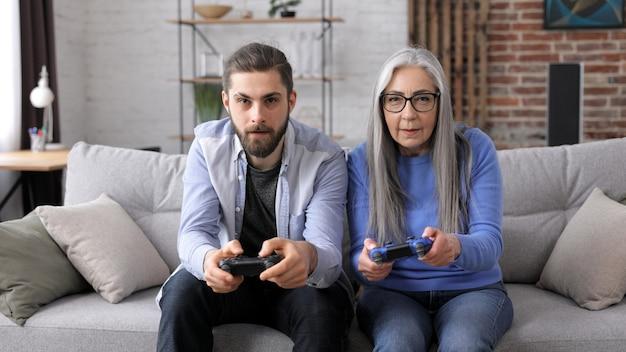 Avó e neto jogando videogame usando gamepads em casa.