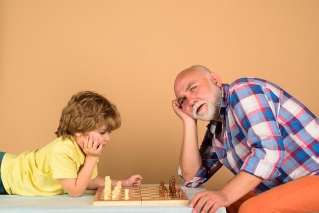 Avô e neto jogando xadrez criança menino jogando xadrez com avô menino pensa ou