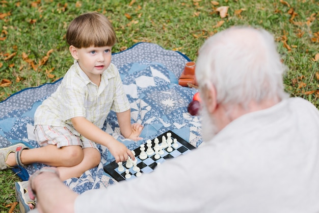 Avô e neto jogando xadrez