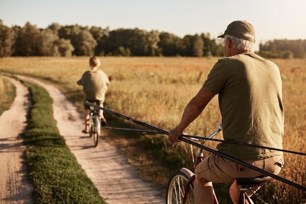 Avô e seu neto vão pescar em bicicletas, vista traseira da família no prado em bicicletas com varas de pesca, homem sênior e jovem vestindo fechamento casual, belo campo e árvores.