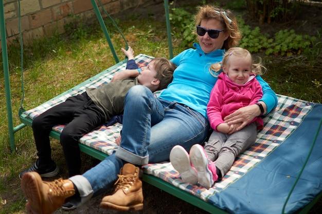 Avó e seus dois netos se divertindo em um balanço de neto e neta relaxando ...