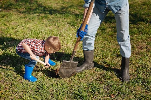 Avô e uma criança de cabelos castanhos trabalhando duro em um jardim, cavando um buraco no chão para uma nova macieira