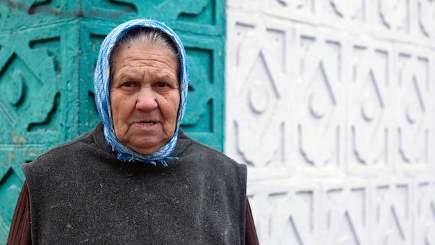 Avó em um lenço no fundo da parede de sua casa, o conceito de velhice.