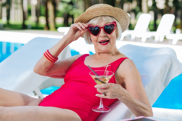 Avó engraçada e fofa com lábios vermelhos brilhantes bebendo um coquetel refrescante de verão