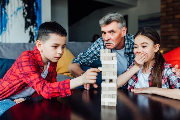 Avô engraçado que joga o jogo de torre de madeira de blocos com filha e filho.