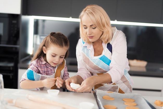 Avó ensina a neta a cozinhar