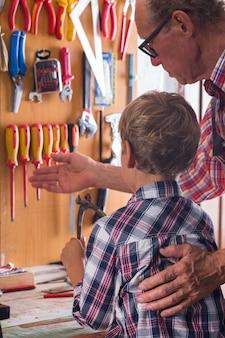 Avô ensina menino a trabalhar na bancada com ferramentas de marcenaria