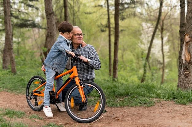 Avô ensinando o neto a andar de bicicleta