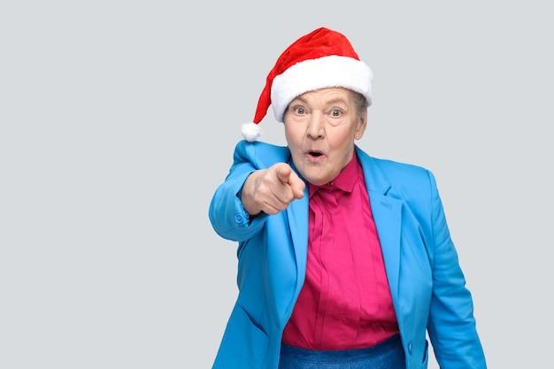 Avó espantada em estilo casual colorido, terno azul e boné vermelho de natal em pé e olhando e apontando o dedo para a câmera com rosto chocado. interno, foto de estúdio, isolado em fundo cinza