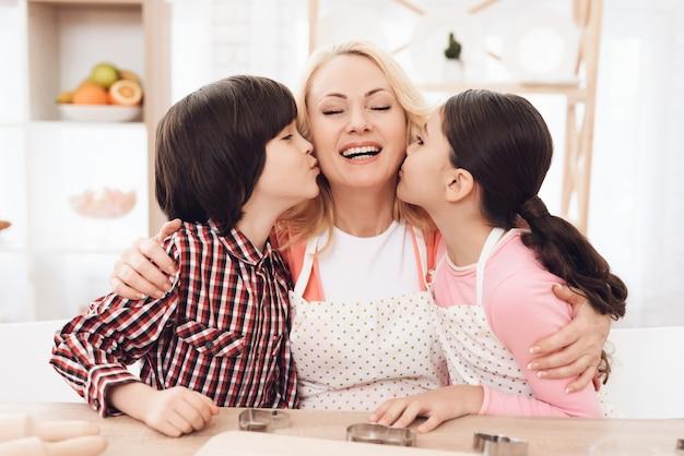 Avó feliz abraçando netos na cozinha