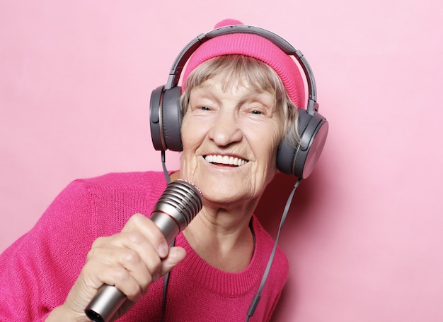 Avó feliz com fones de ouvido e microfone sobre fundo rosa, cantor engraçado