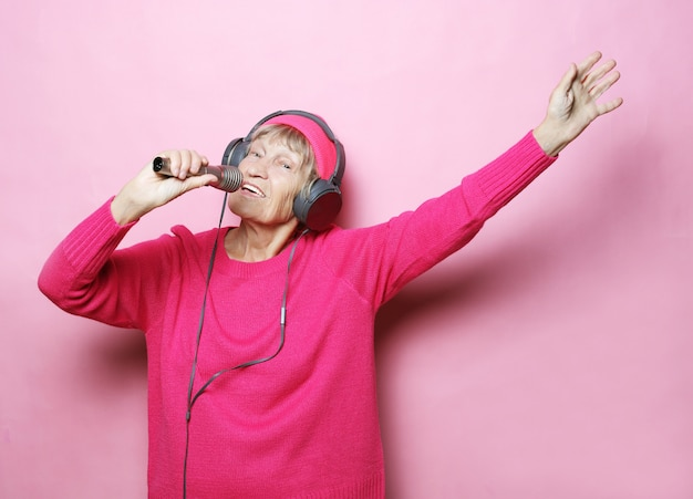 Avó feliz com fones de ouvido e microfone sobre rosa