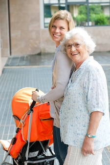 Avó feliz e sorridente caminhando com o neto e empurrando um carrinho de bebê, família de três gerações ao ar livre
