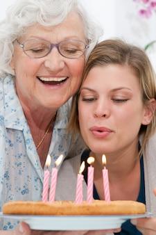 Avó feliz e sorridente comemorando e dando um bolo de aniversário para o neto em casa