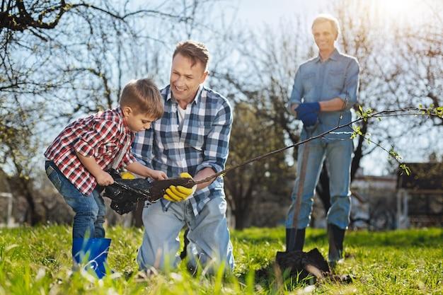Avô feliz parado com uma pá atrás, olhando para o neto e o filho plantando uma macieira