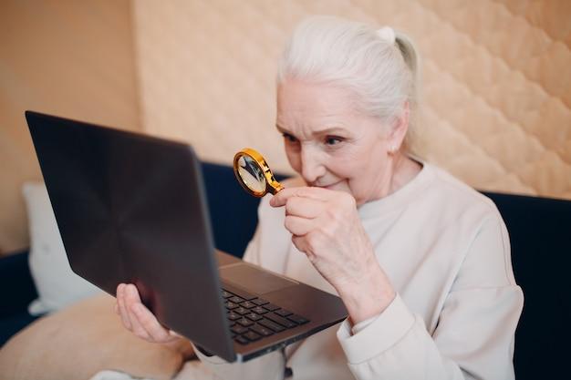 Avó idosa aprende a trabalhar em casa no laptop e na internet com lupa