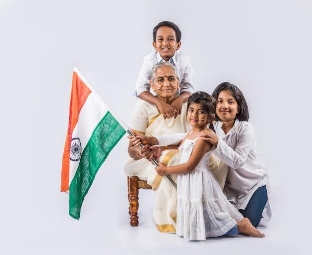 Avó indiana e filhos comemorando o dia republicano ou o dia da independência com rostos pintados com tricolor segurando a bandeira nacional, isolada sobre fundo branco