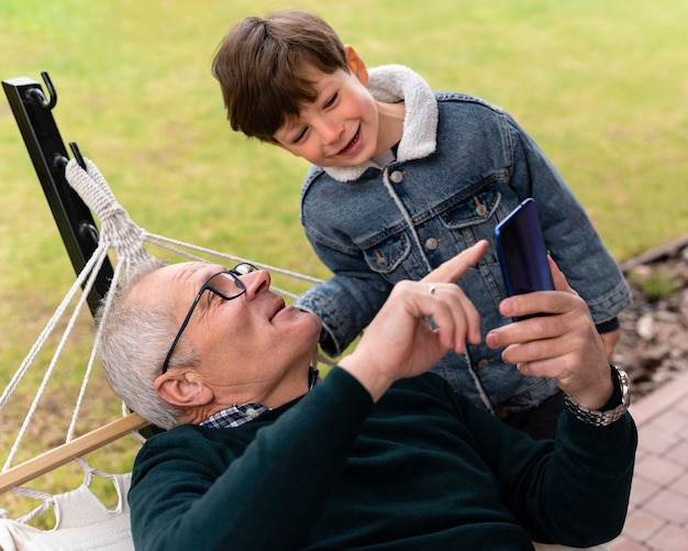 Avô lá fora com seu neto segurando um telefone