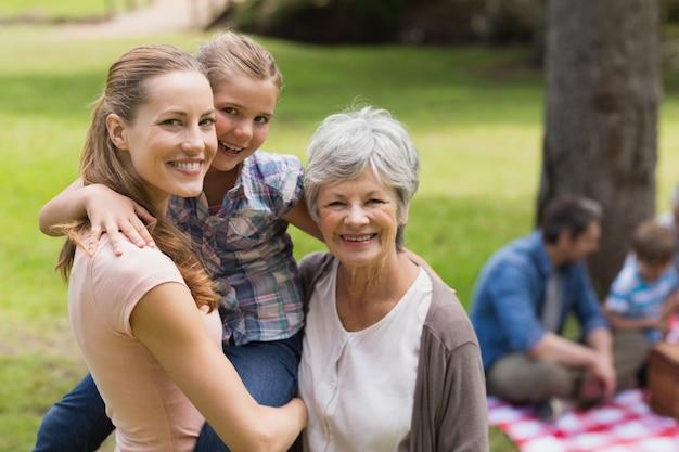 Avó, mãe e filha com a família em segundo plano no parque