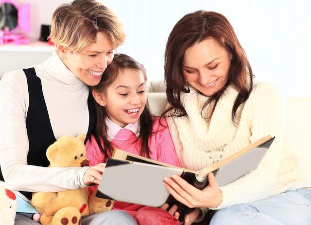 Avó, mãe e filha lendo um livro juntas