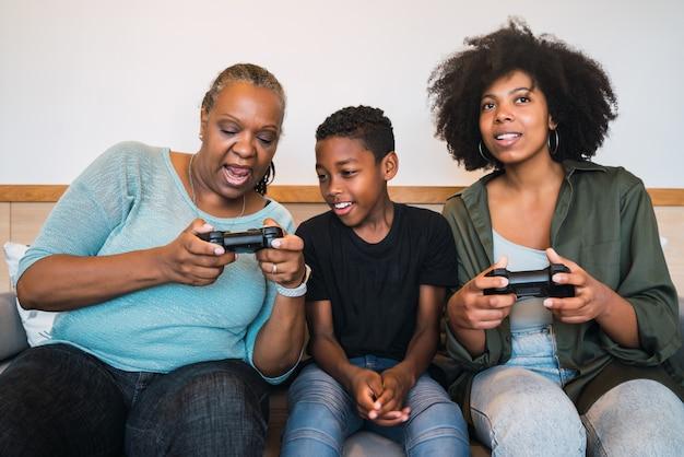 Avó, mãe e filho jogando videogame em casa.