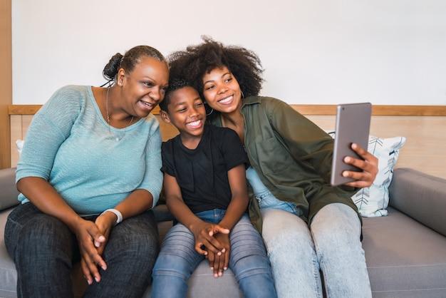 Avó, mãe e filho tomando uma selfie com tablet digital.