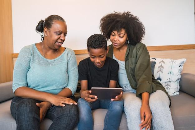 Avó, mãe e filho usando tablet digital.