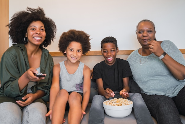 Avó, mãe e filhos assistindo a um filme em casa.
