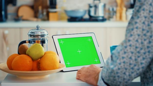 Avô olhando para o tablet pc com tela verde durante o café da manhã na cozinha. idoso com maquete isolada de chroma key para fácil substituição