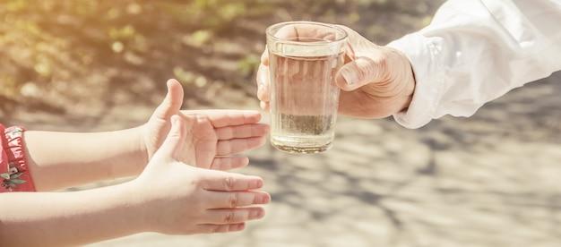 Avó que dá um vidro da agua potável a uma criança. foco seletivo.