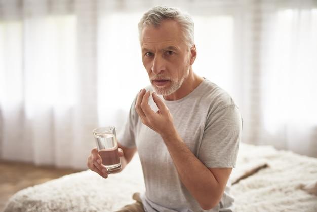 Avô que toma comprimidos na dor crônica da manhã.