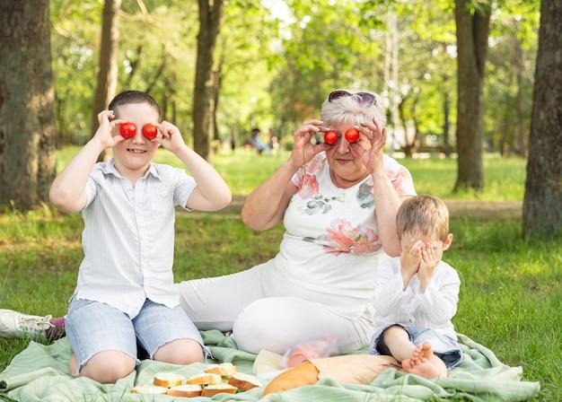 Avó rindo e netos brincando, passando o fim de semana, vinham visitar a vovó velha, se divertindo lá fora