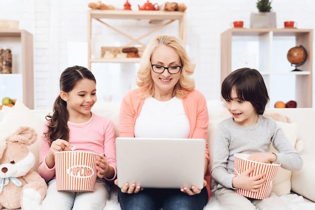 Avó sagacidade crianças assistindo filme no laptop