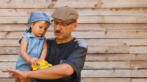 Avô, segurando neto com carro de brinquedo