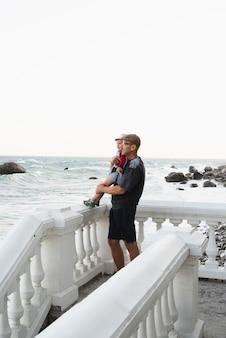 Avô, segurando neto e olhando para o mar