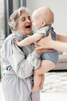Avó segurando o neto em casa