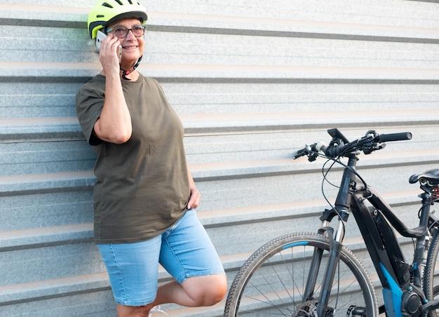 Avó sênior com telefone celular encostado em uma parede de metal estilo de vida saudável com bicicleta