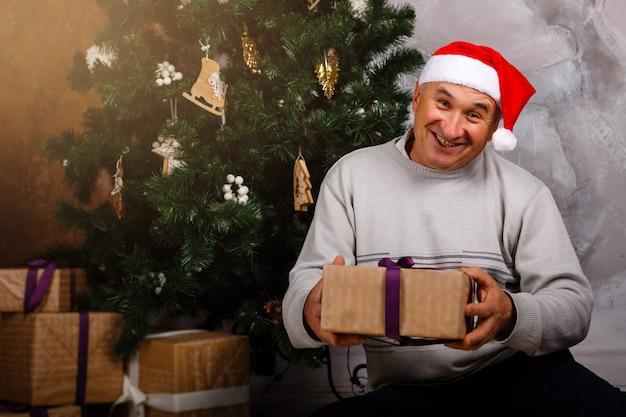 Avô senta-se perto de uma árvore de natal em uma cadeira com um grande presente