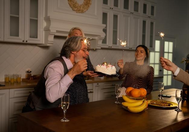 Avô soprando velas em um bolo de aniversário e fazendo um pedido sentado atrás da mesa da cozinha