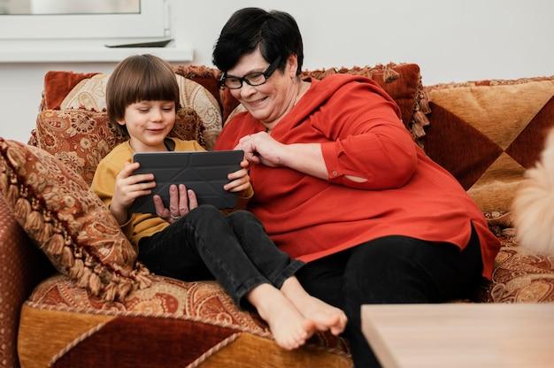 Avó sorridente brincando com o neto no tablet