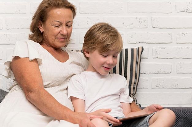 Avó sorridente e criança com tablet