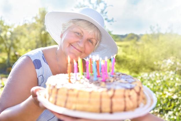 Avó sorridente segurando um bolo caseiro de aniversário. celebração de família