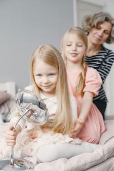 Avó trançando o cabelo da neta. segunda neta fazendo a trança da irmã. casa aconchegante, relações familiares.