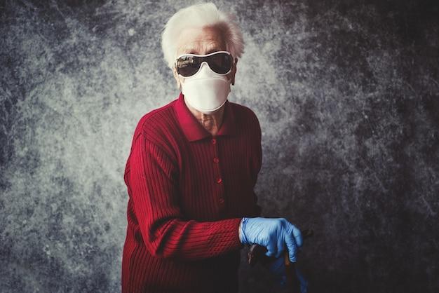 Avó velha proteger-se da infecção por coronavírus com luvas médicas e máscara respiratória