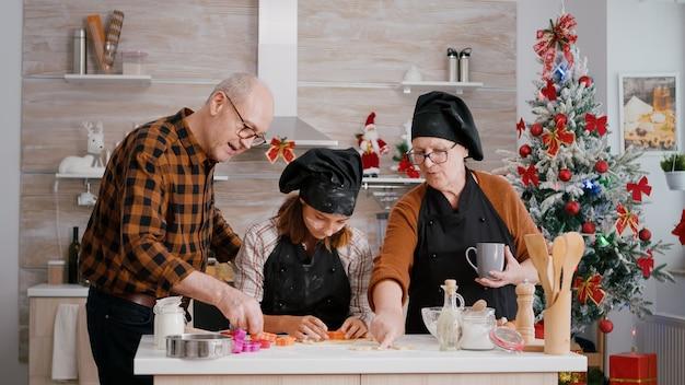 Avós ajudando neto a preparar pão de mel caseiro usando formato de biscoito