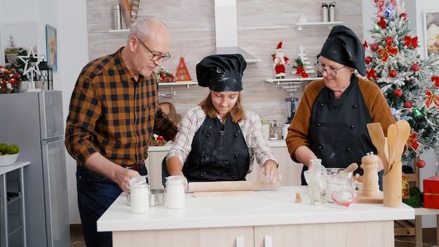 Avós ajudando o neto a preparar a tradicional massa caseira