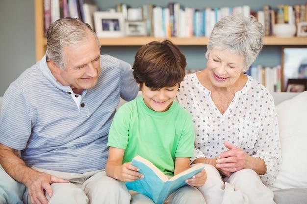 Avós, ajudando o neto durante a leitura do livro