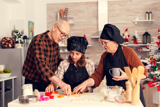 Avós ajudando sobrinha com sobremesa no dia de natal
