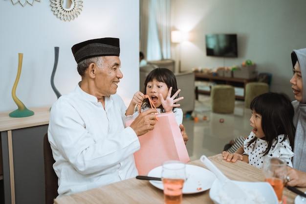 Avós asiáticos dando um presente aos netos durante a celebração do eid mubarak em casa