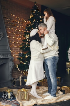 Avós com a neta. comemorando o natal em uma casa aconchegante.